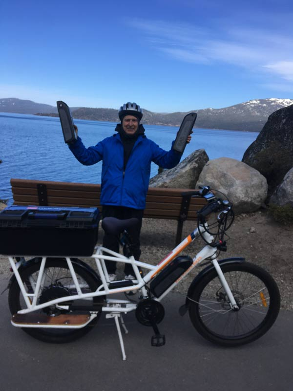 John holding up his two spare batteries in front of Sunride, Jr. with Lake Tahoe in the background.