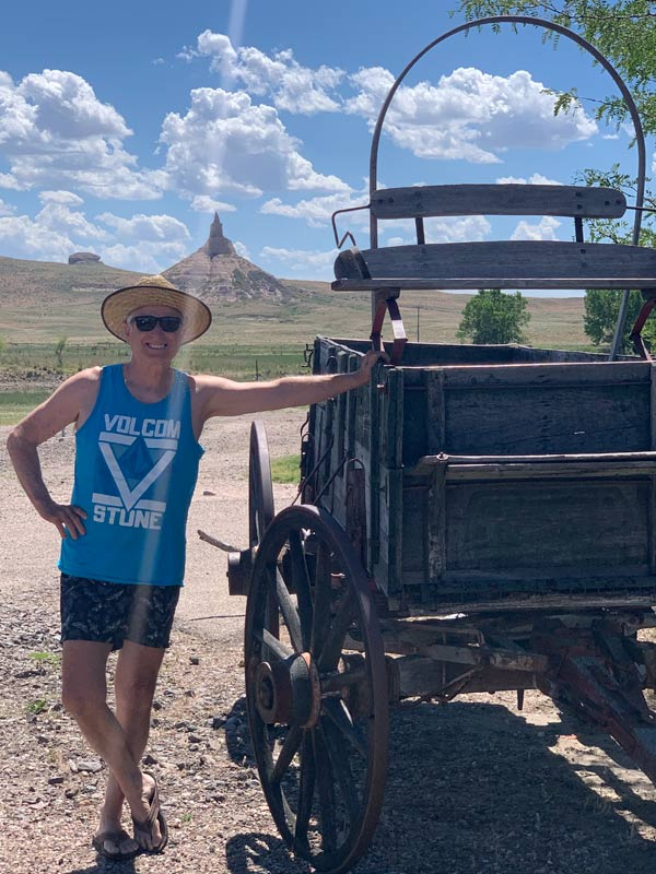 John beside a wagon with Chimney Rock in Western Nebraska in the background