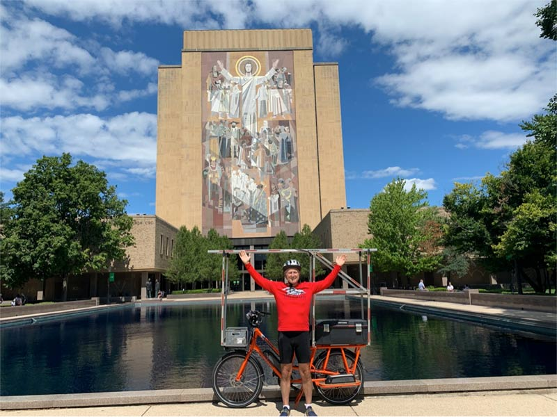 "John and Sunride in front of Notre Dame University reflecting pool and mural of Christ on the Hesburgh Library, commonly known as ""Touchdown Jesus."""