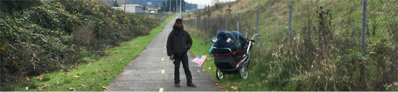Homeless man with an American flag on the buggy holding all his belongings