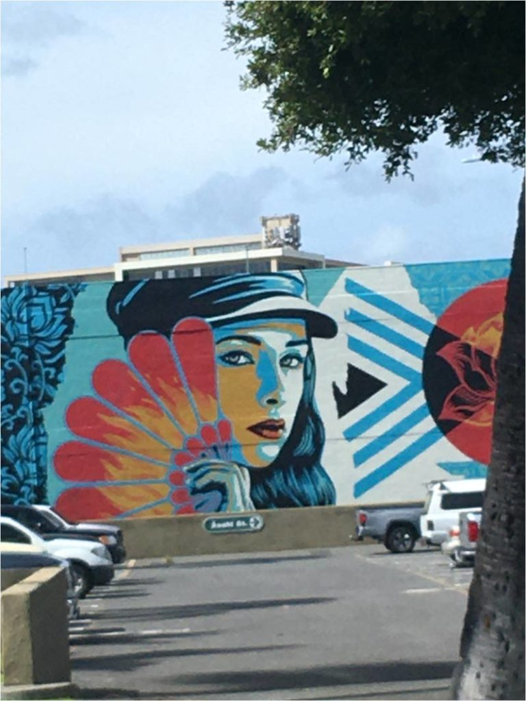 Mural of a beautiful, mysterious woman in a hat holding a fan