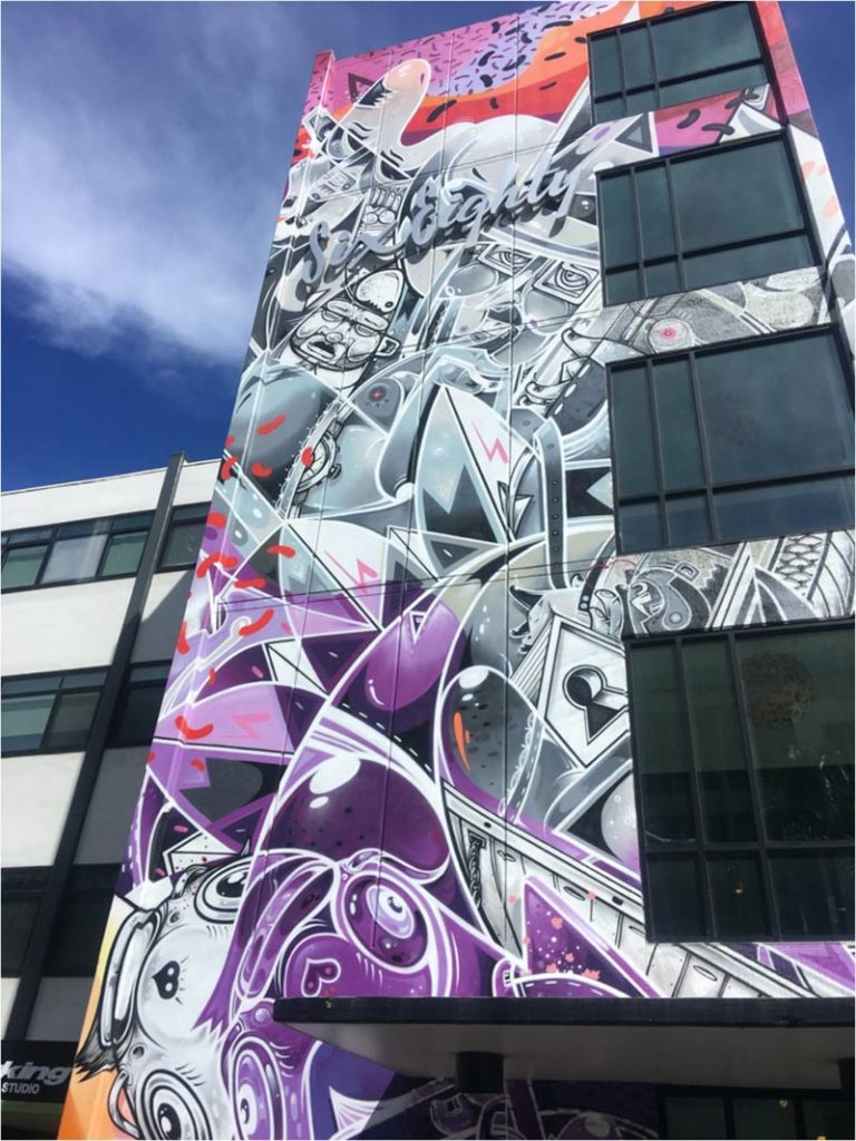 Modern art mosaic on a tall building with purple, silver and muted green accents