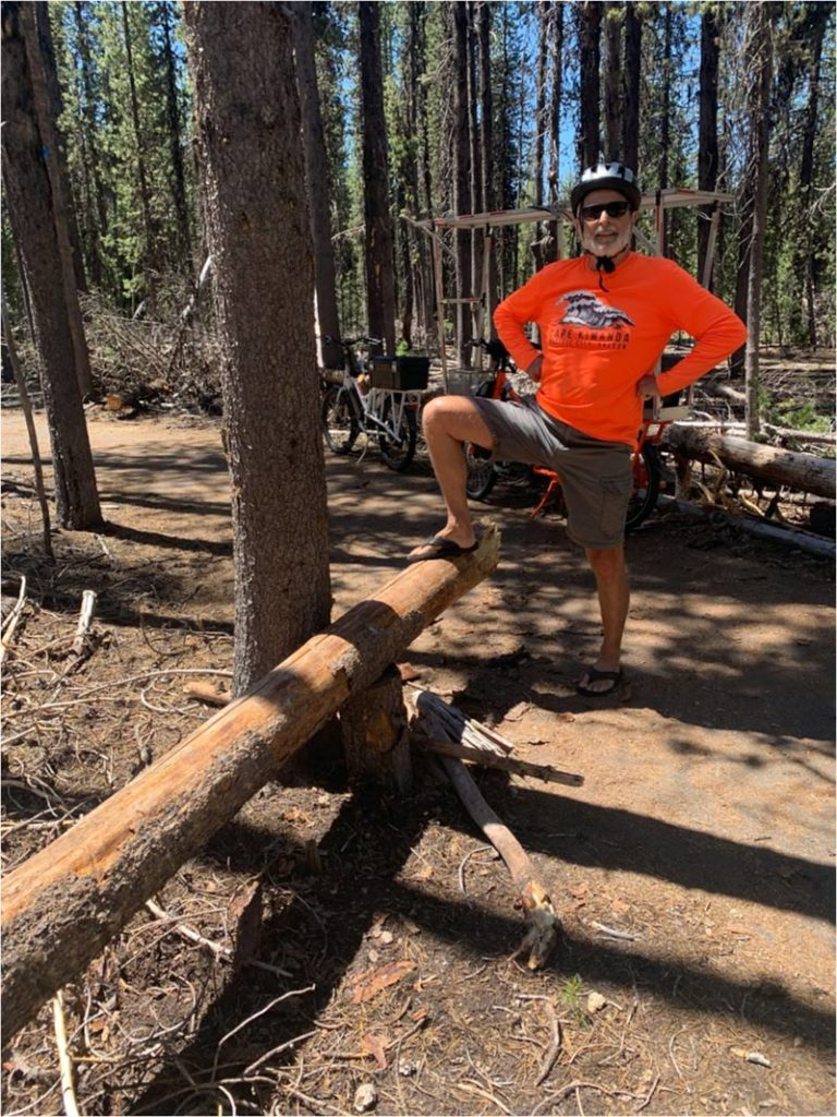 John with one foot resting on the conquered log.